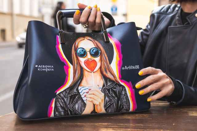 person holding black tote bag
